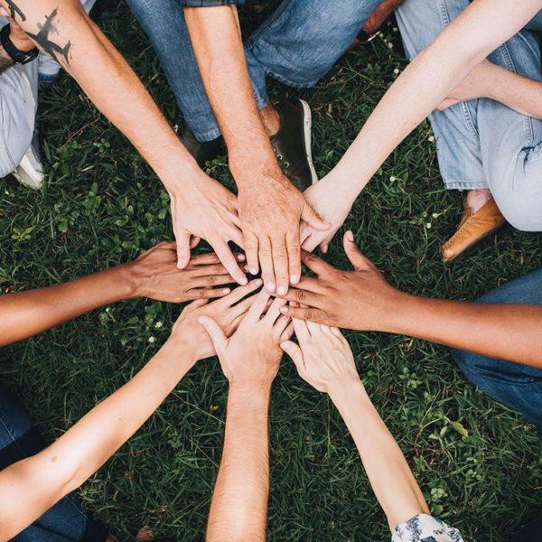 Eine Gruppe von Menschen hält Hände übereinander